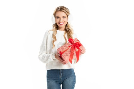 beautiful smiling young woman in winter outfit holding gift isolated on white