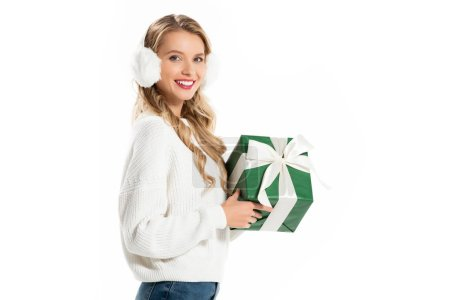 beautiful girl in winter outfit holding green present isolated on white