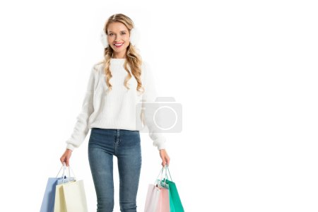 beautiful happy girl in winter outfit holding shopping bags isolated on white