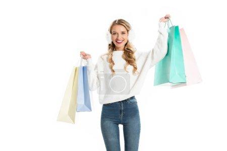 Photo pour Belle jeune femme souriante en tenue d'hiver portant des sacs shopping isolés sur blanc - image libre de droit