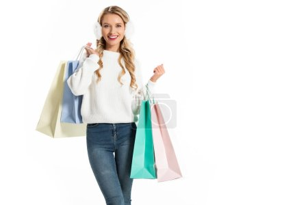 Photo for Cheerful woman in winter outfit holding shopping bags isolated on white - Royalty Free Image