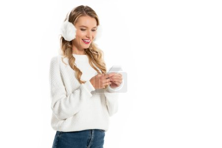 beautiful smiling woman in winter earmuffs using smartphone isolated on white
