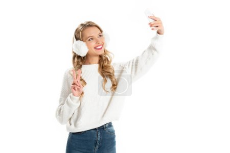 cheerful girl showing victory sign while taking selfie on smartphone isolated on white