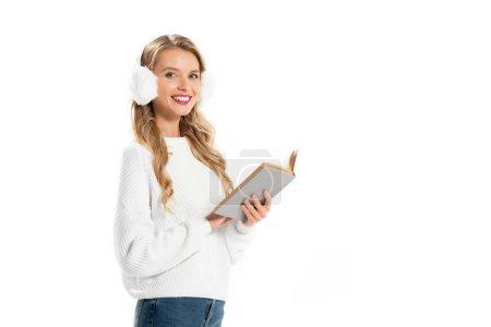 Photo pour Jeune fille souriante dans le cache-oreilles hiver tenant livre isolé sur blanc - image libre de droit