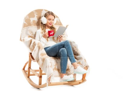 happy girl with cup of coffee reading book while sitting in rocking chair isolated on white