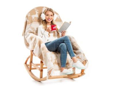 Photo pour Jeune femme souriante tenant Coupe du livre et du café tout en étant assis dans le fauteuil à bascule isolé sur blanc - image libre de droit