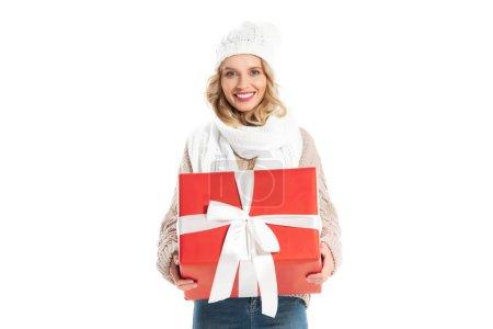 Photo pour Souriante jeune fille en tenue d'hiver tenue grand cadeau rouge isolé sur blanc - image libre de droit
