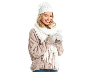 cheerful blonde woman in winter sweater and hat using smartphone isolated on white