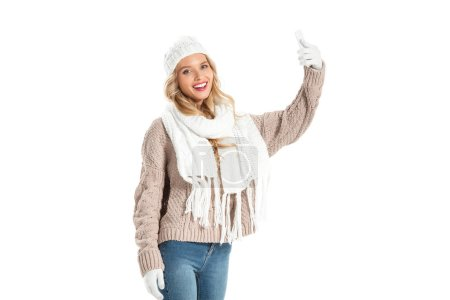 young smiling woman in winter sweater taking selfie on smartphone isolated on white