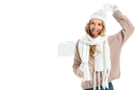 Cheerful young woman in beige knitted sweater, white hat and scarf showing tongue isolated on white