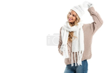 Cheerful young woman in beige knitted sweater, white hat, mittens and scarf smiling isolated on white