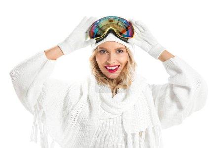 Belle jeune femme en vêtements d'hiver avec ski lunettes sur la tête en souriant et en regardant la caméra isolé sur blanc
