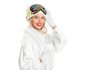 Nice young woman in warm knitted clothes and ski goggles smiling and looking at camera isolated on white