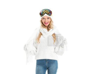 attractive woman in white knitted sweater, hat, scarf and mittens with ski goggles on head smiling and looking at camera isolated on white