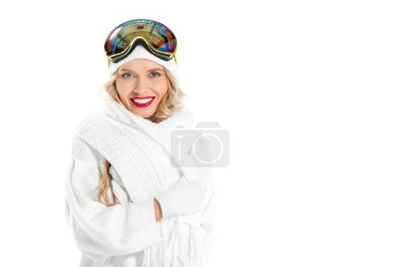 Beautiful woman in winter clothes with ski goggles on head smiling, looking at camera and shivering isolated on white