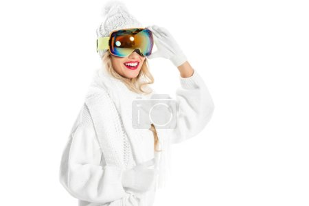 joyful woman in white knitted sweater, hat and mittens putting on ski goggles isolated on white