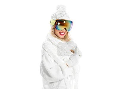 Photo pour Jeune femme en vêtements blancs chauds et lunettes de ski sourire isolée sur blanc - image libre de droit