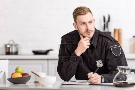 Photo for Thoughtful policeman sitting at kitchen table - Royalty Free Image