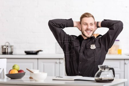 Smiling police officer with hands on head sitting at kitchen table