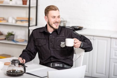 Photo for Handsome police officer sitting at kitchen table, smiling and drinking coffee - Royalty Free Image