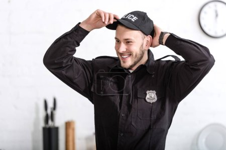 handsome police officer smiling and putting on cap at kitchen