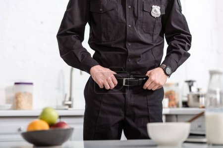 cropped view of police officer standing next to kitchen table