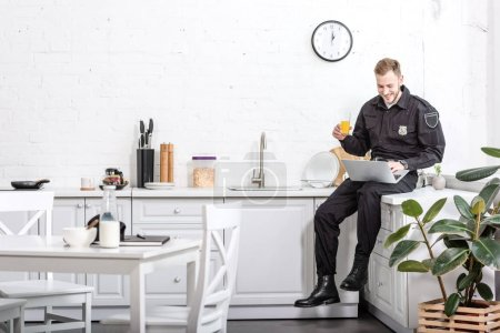 Photo for Young policeman sitting on table, drinking orange juice and using laptop at kitchen - Royalty Free Image