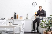 Young policeman sitting on table, drinking orange juice and using laptop at kitchen