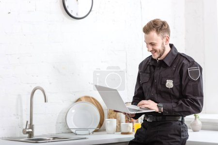 Photo for Handsome man in police uniform smiling and using laptop at kitchen - Royalty Free Image