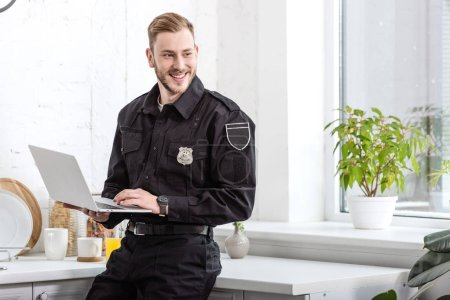 Photo for Handsome policeman smiling and using laptop at kitchen - Royalty Free Image