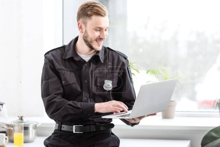 Photo for Smiling police officer standing and using laptop by kitchen window - Royalty Free Image