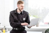 smiling police officer standing and using laptop by kitchen window