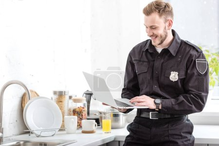 smiling police officer standing and using laptop at kitchen