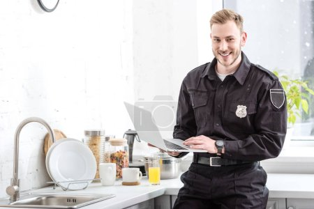 Photo for Smiling police officer standing with laptop at kitchen - Royalty Free Image
