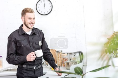 Photo for Handsome man in police uniform drinking coffee at kitchen - Royalty Free Image