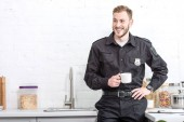 Handsome police officer drinking coffee at kitchen