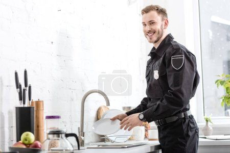 Handsome police officer smiling and washing plate at kitchen
