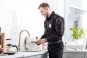 Smiling police officer washing plate at kitchen