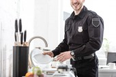 cropped view of handsome policeman washing plate at kitchen