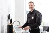 Handsome police officer washing dishes at kitchen