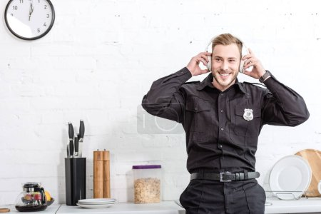 Photo for Handsome policeman listening to music at kitchen - Royalty Free Image