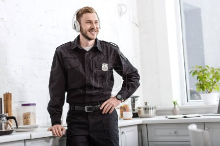 smiling police officer listening to music with headphones at kitchen