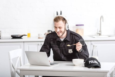 Handsome police officer eating cornflakes and using laptop at kitchen