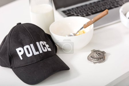 police cap, bowl with cornflakes, police badge and laptop on table