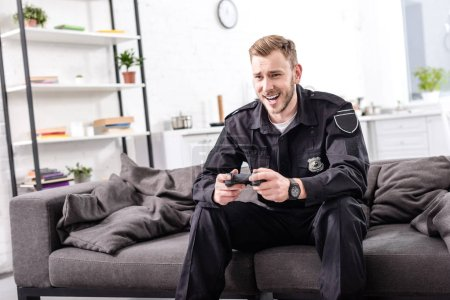 laughing police officer with gamepad sitting on couch and playing video game