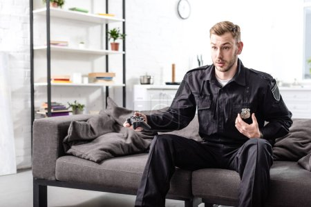 Photo for Surprised police officer sitting on couch with gamepad and playing video game - Royalty Free Image