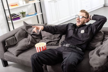 policeman in 3d glasses sitting on couch and  watching movie