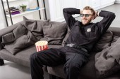 policeman in 3d glasses with hands on head sitting on couch and watching movie