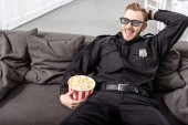 Smiling policeman in 3d glasses with hand on head sitting on couch with striped popcorn bucket and watching movie