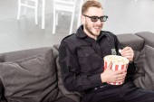 policeman in 3d glasses sitting on couch, eating popcorn and watching movie